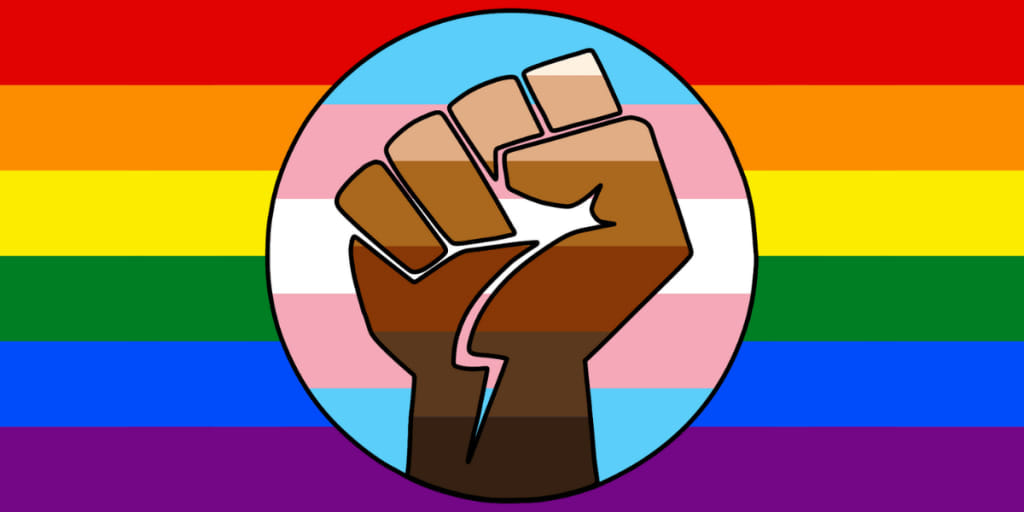The background flag illustrates our support of LGBTQA+ communities. The center flag in a cricle represents our support for the transgender community. Overlaid on top of that, a multi-hued fist indicates that Black Lives Matter.